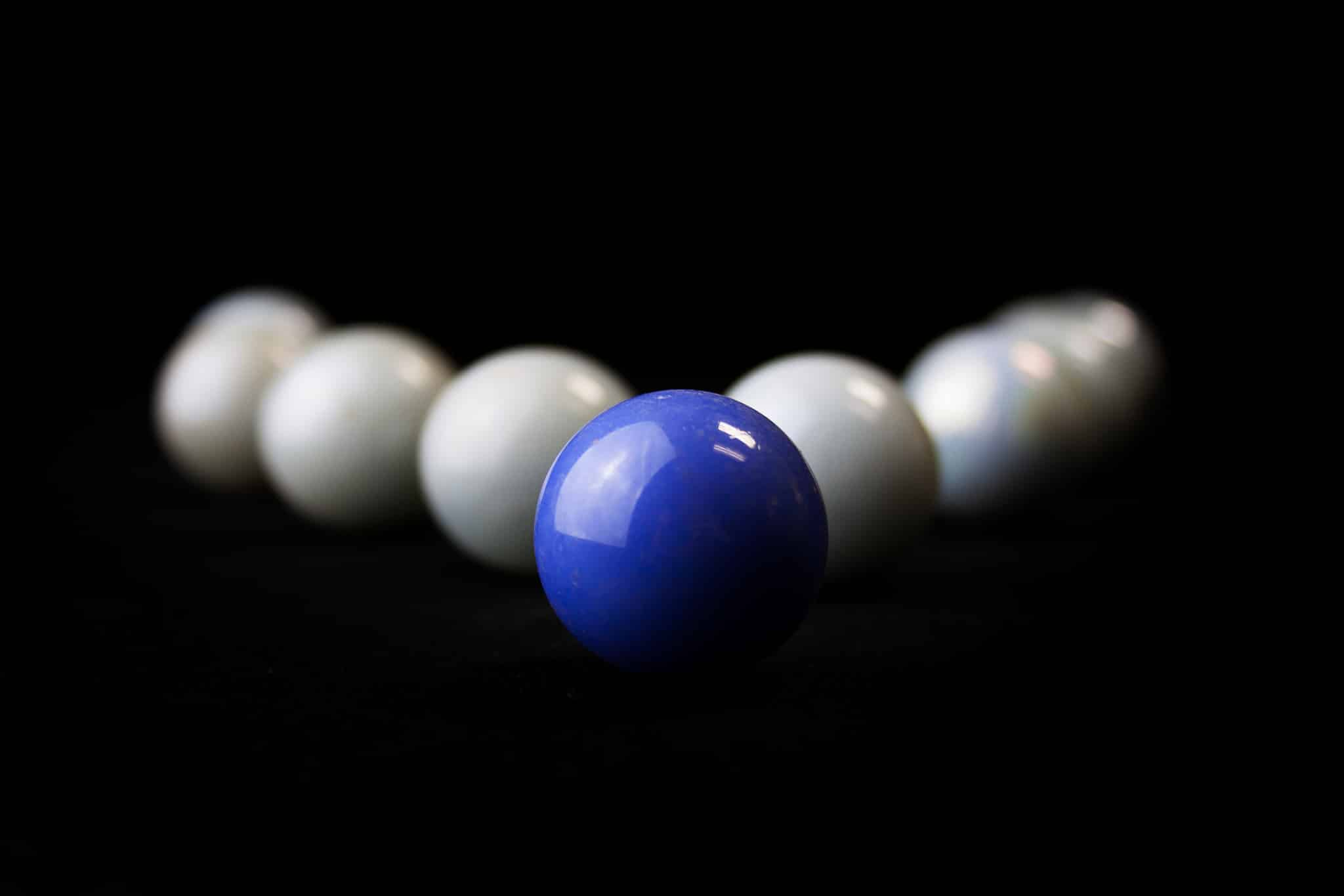 string of white marbles with 1 blue in the front