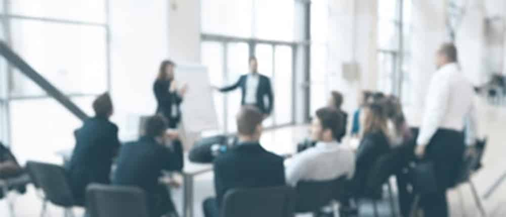 blurred image of a group of people at a conference table