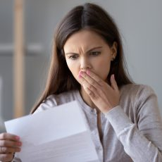 Shocked stressed young woman reading document letter from bank about loan debt financial problem