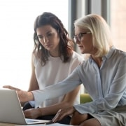 young woman and older woman looking at computer screen