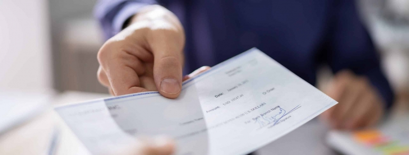 Businessperson Hands Giving Cheque To Other Person