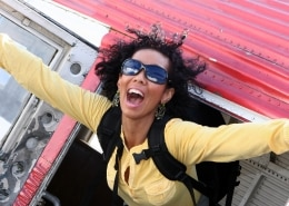smiling woman jumping out of a red plane