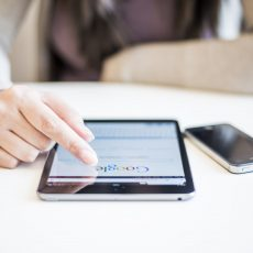 Woman hands holding and touching on Apple iPad mini with Google search web page on a screen.