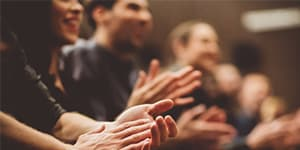 Blurred photo of people clapping during a speech or training session